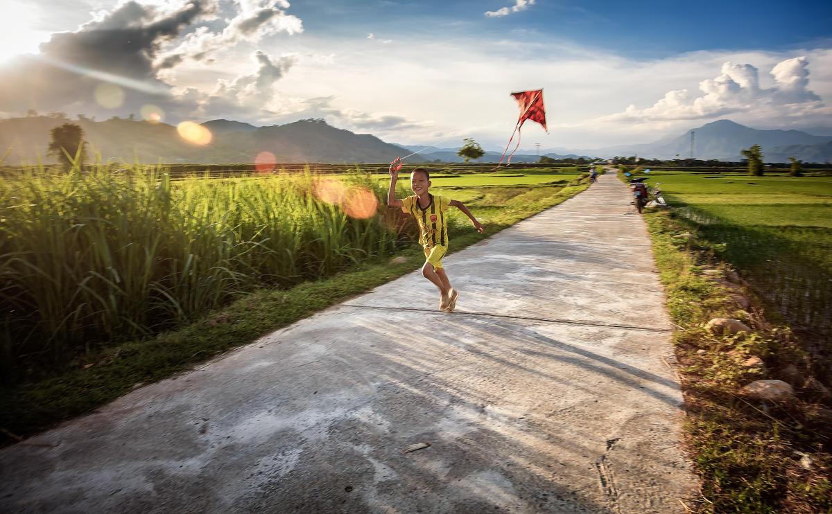 Enfant jouant avec un cerf-volant au Vietnam.
