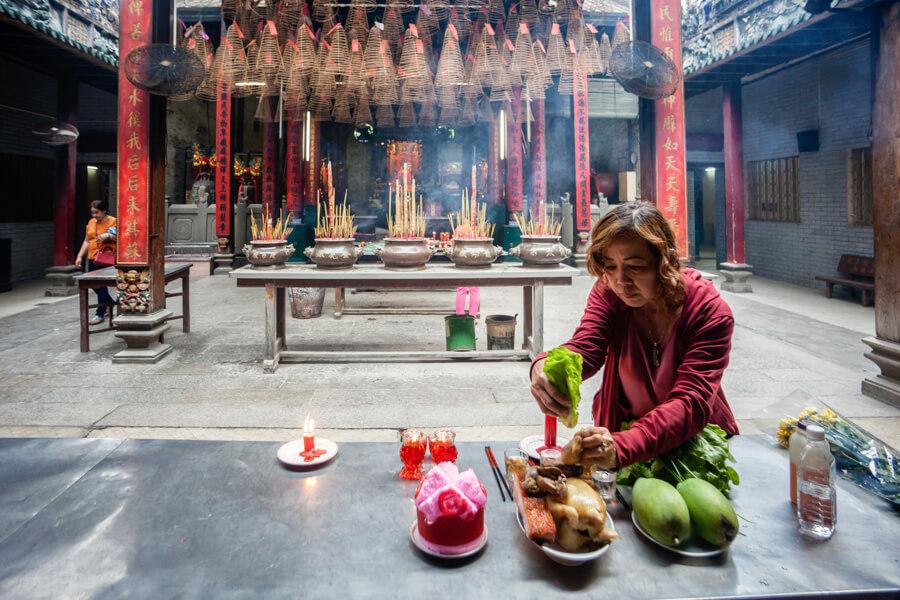 femme faisant des offrandes dans un temple.