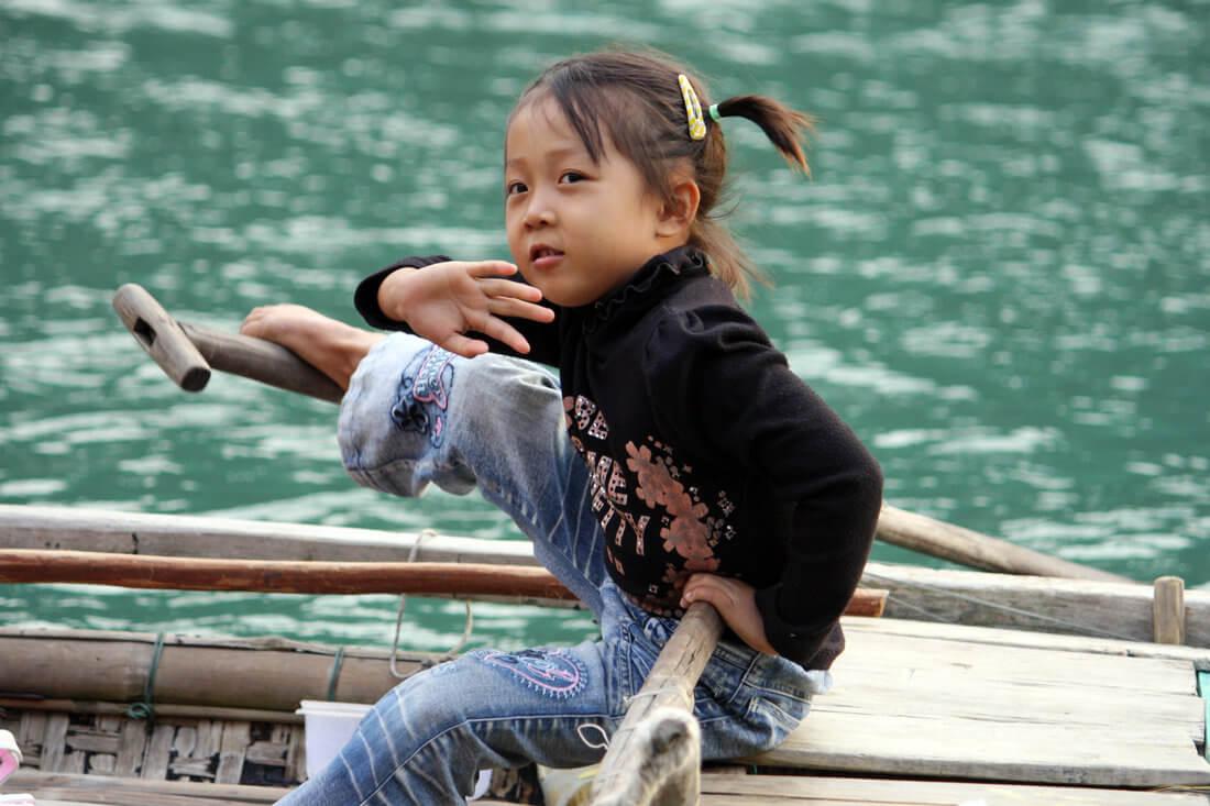 petite fille barrant une barque traditionnelle.