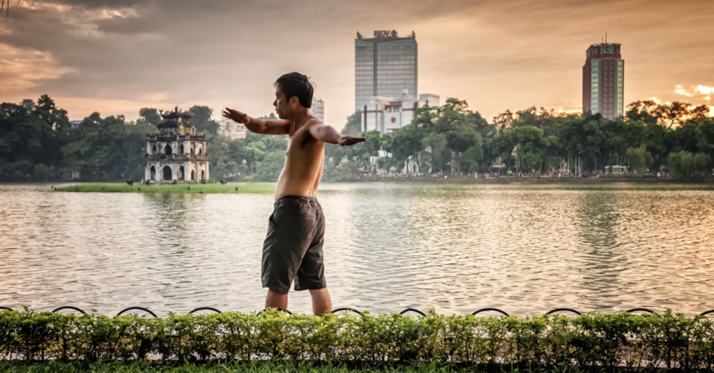 Homme faisant des excercices au bord de l'eau au Vietnam.